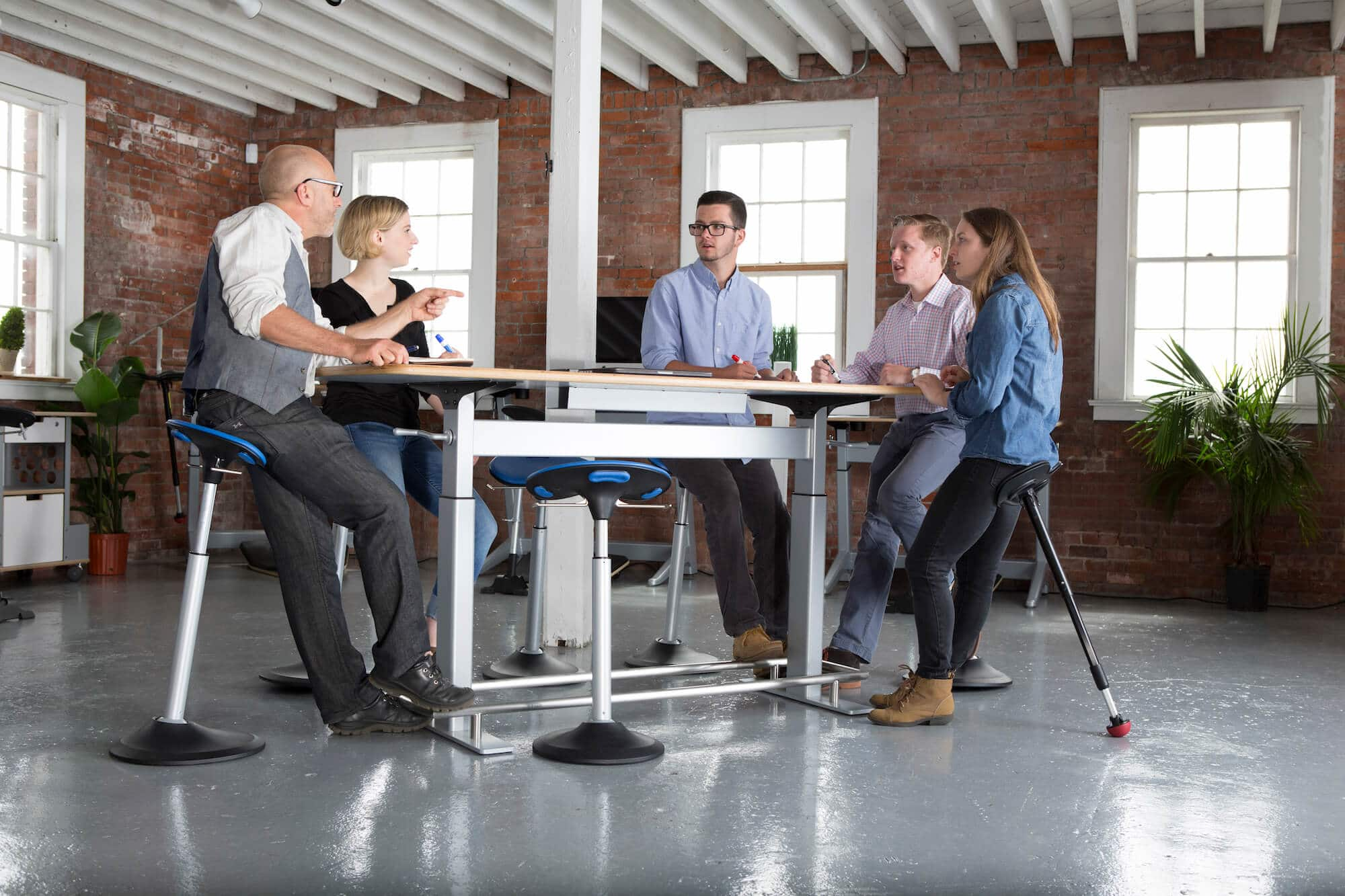 leaning seat at conference table in brick hipster office setting