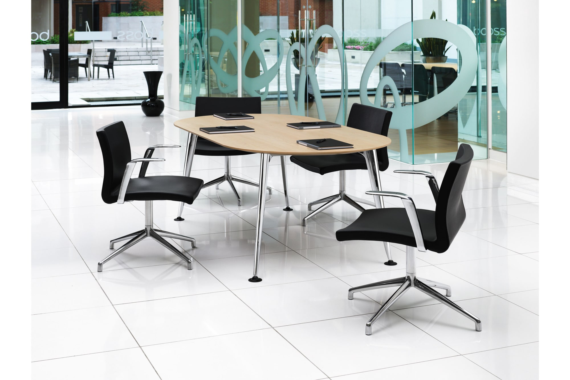 modern table with light wood top and black chairs