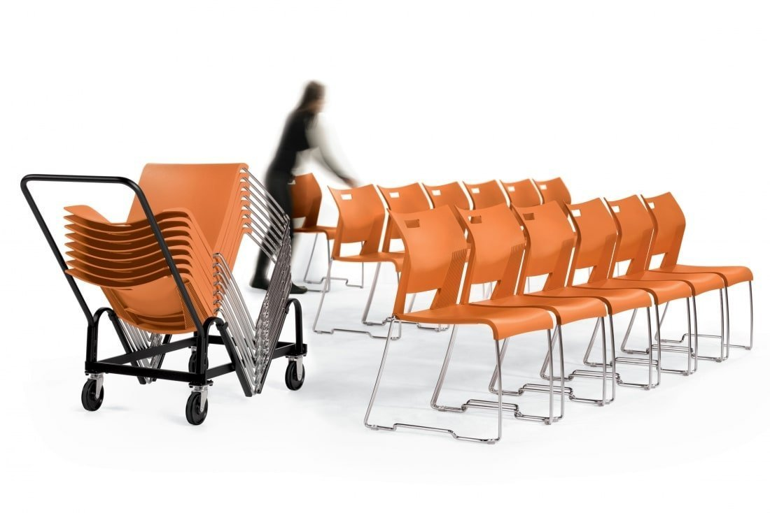 Woman using high-density stacking chair dolly to move orange duet stacking chairs