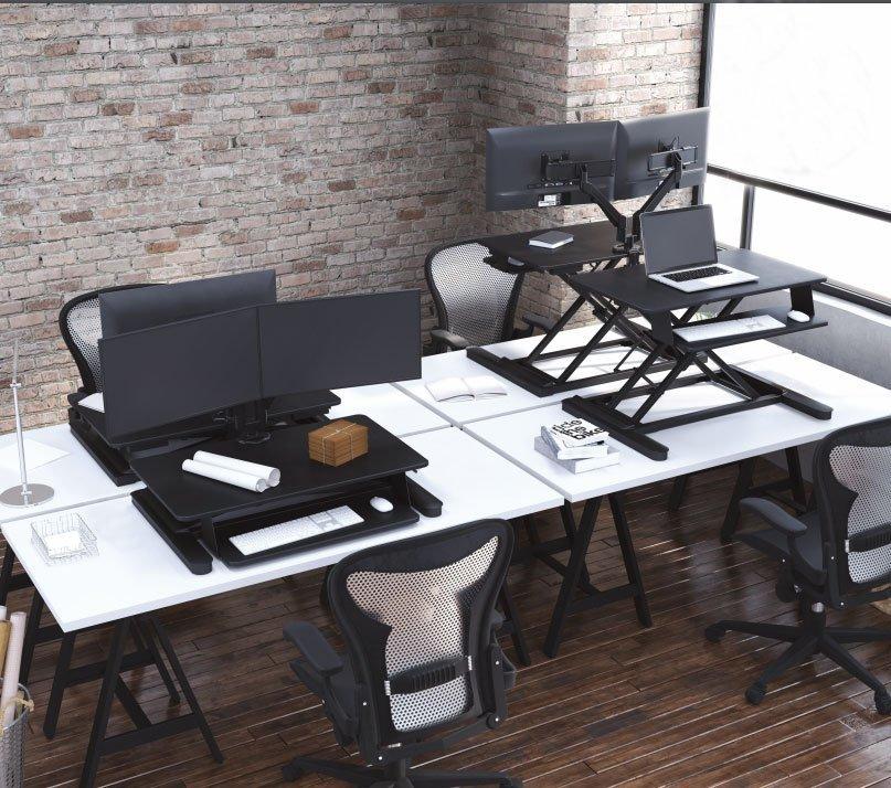 standing desk on top of modern table desks in a loft workspace