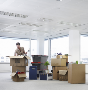 moving boxes and business woman in an empty office