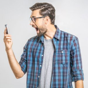 man looking at smartphone with a shocked look on his face
