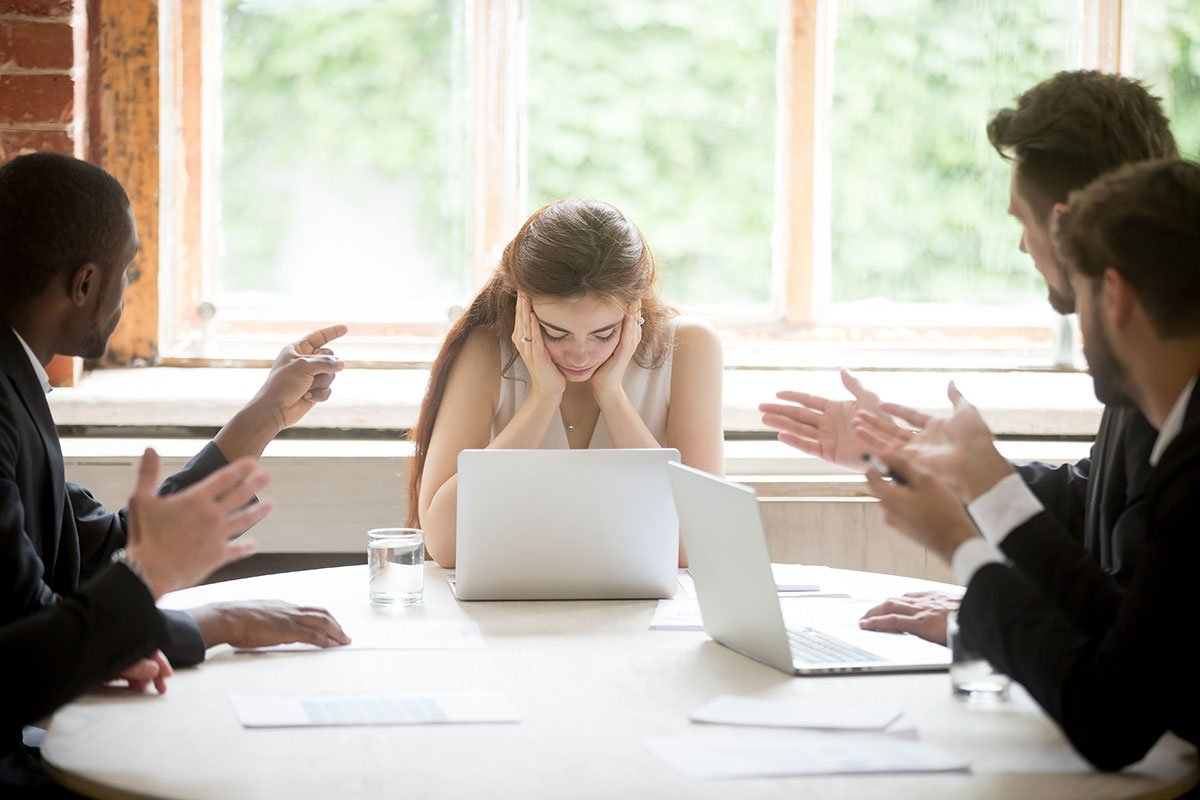 woman at the head of a meeting that looks stressed