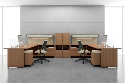 Studio shot of two L-shaped desks, with full sized windows on each side. A Graphic posture back chair is placed at each workstation.