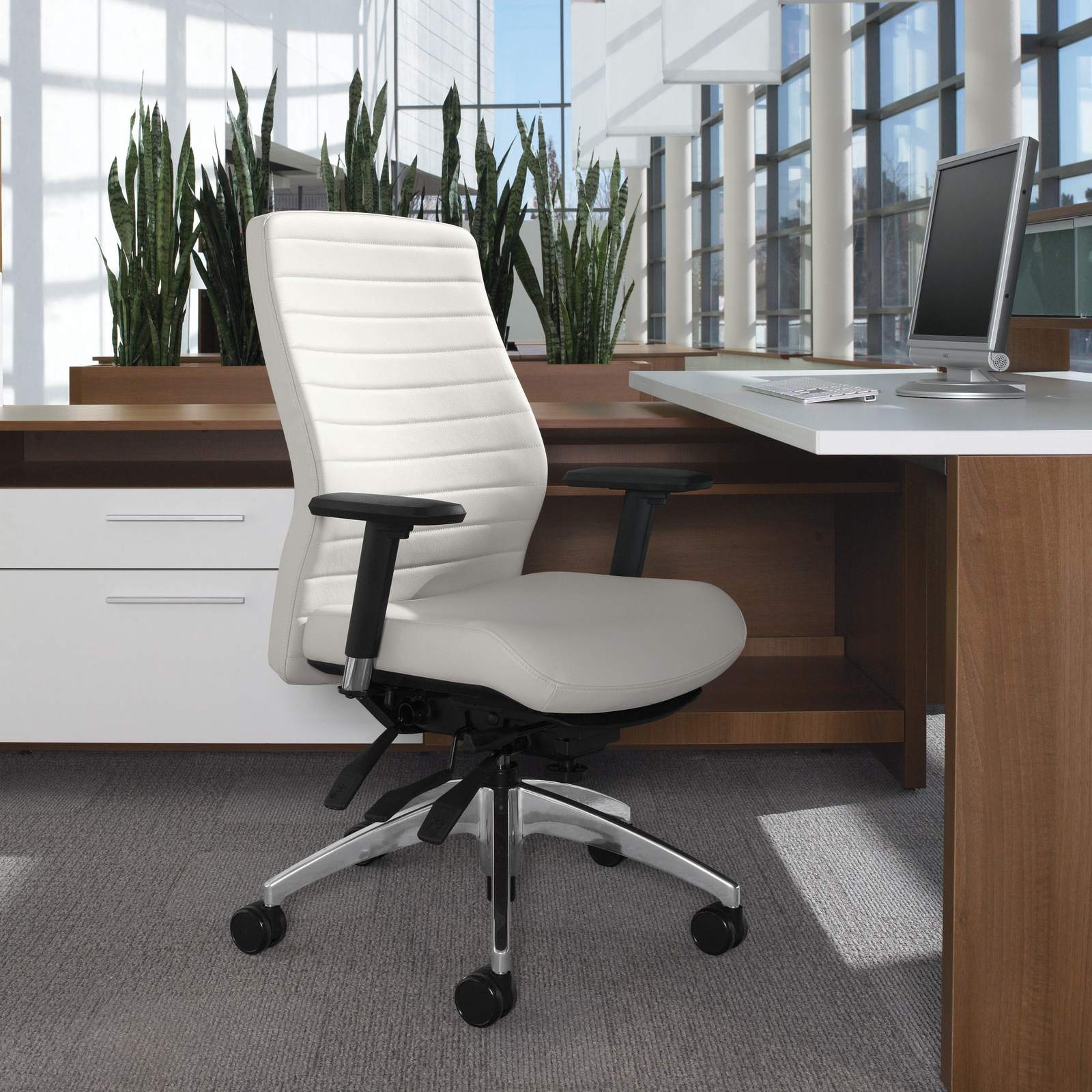 Studio photography of a medium backed Aspen office chair, seated at a wooden workstation.