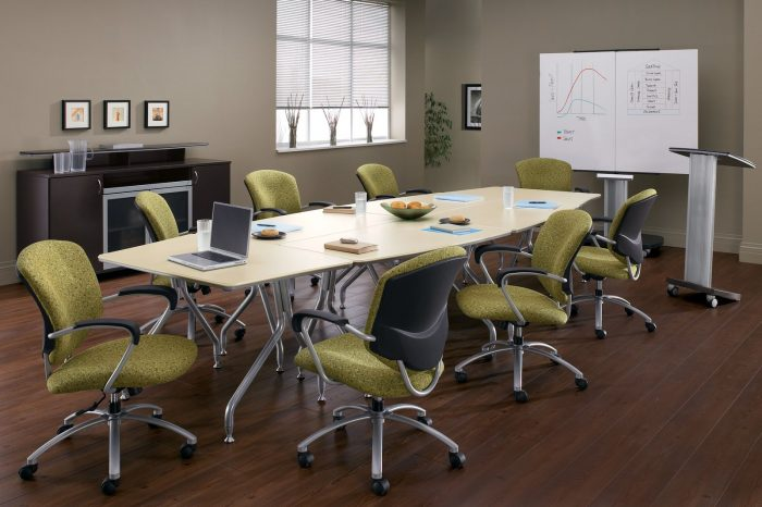 Studio photograph of six 5331-2 model Supra chairs placed at a long onference table. In front is a podium and white board.