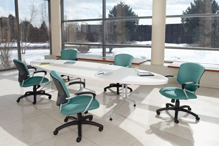 Studio photograph of five Supra rolling chairs placed at a long oval conference table. Tall and wide paned windows show a snowy area of trees.