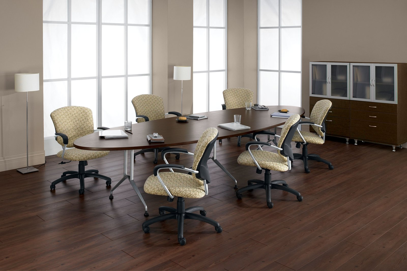 Studio photograph of six 5331-4 model Supra chairs placed at an oval conference table. Paned windows bring in light from the corner.