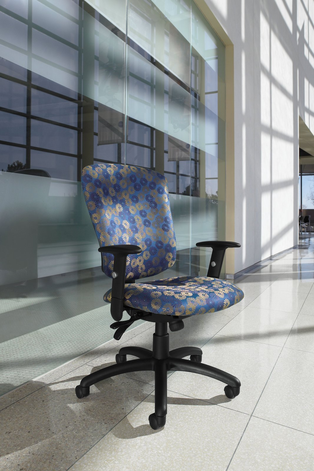 Studio shot a high backed Supra office chairs. The seat and back cushions have a blue and gold floral pattern.