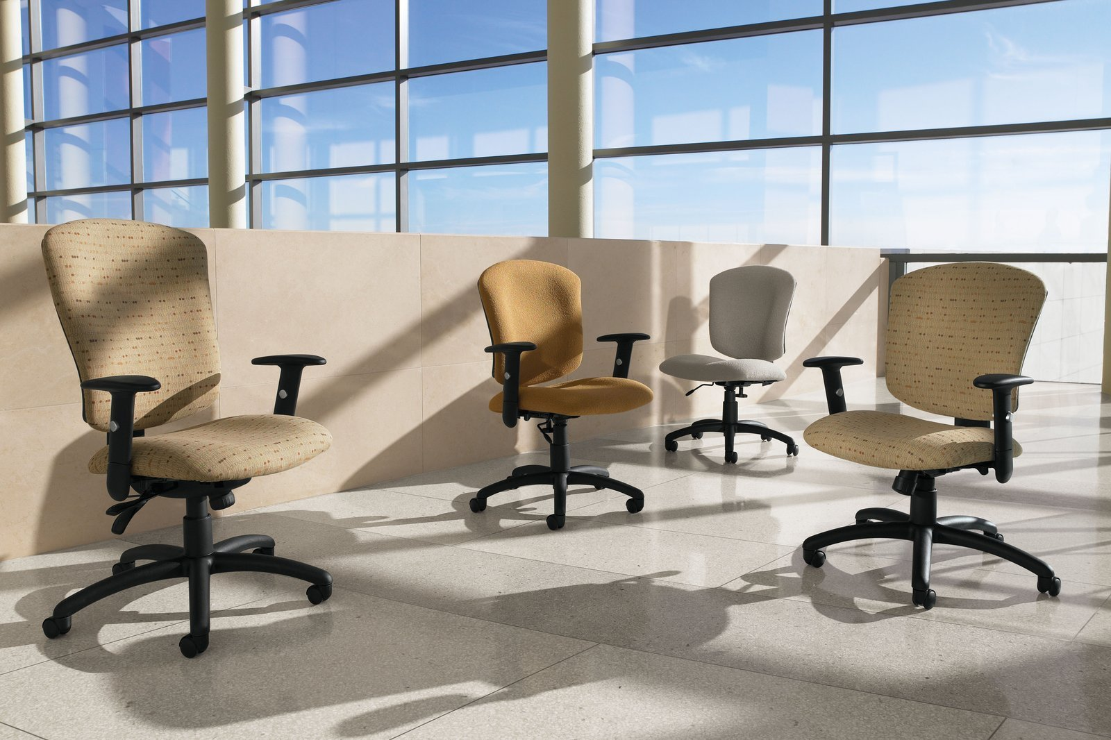 Studio shot of four Supra X office chairs on the mezzanine. One high backed model of this chair is next to a trio of medium backed chairs, an armless chair in back.