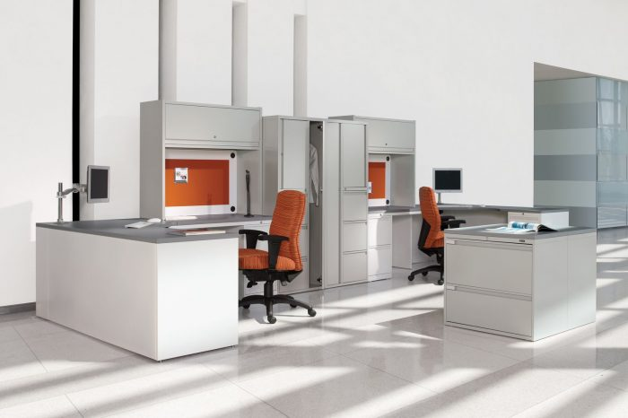 Studio Shot of Two large reception desks and cubicles, with a Synopsis chair placed at each. Behind it are some tall cabinets.