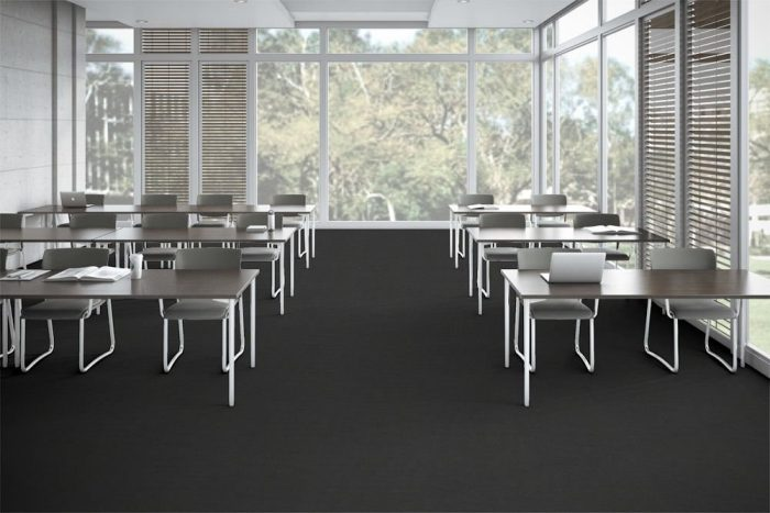 Accelerate flooring in a classroom setting. Tall windows allow light in from the outside.
