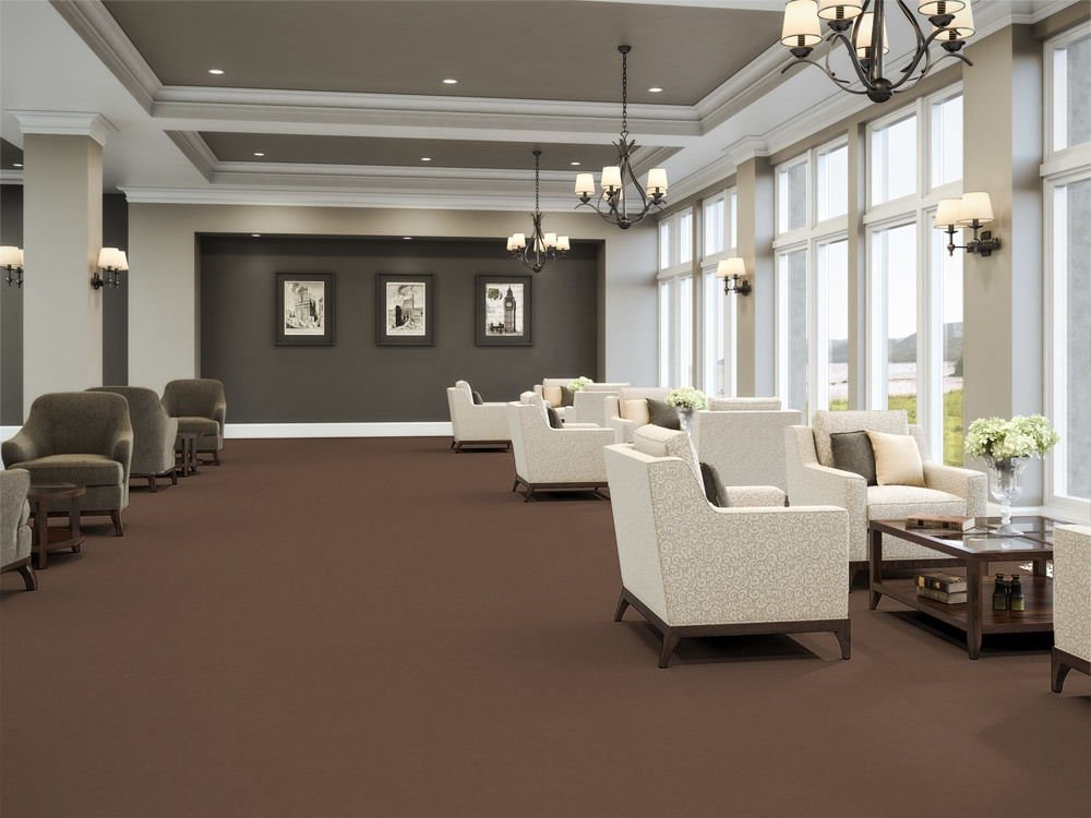 Accelerate flooring in a common area of the senior center. Tall windows on one side bring light in from outside.