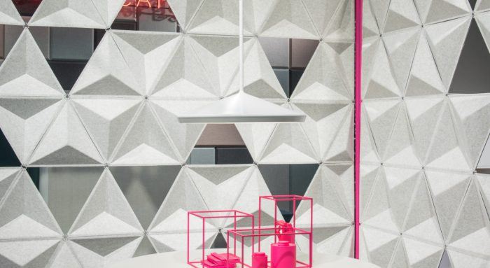 Studio photography into a corner, formed by two sets of Aircone acoustics. A round white table holds a pink wire display. The foam material forms geometric shapes.