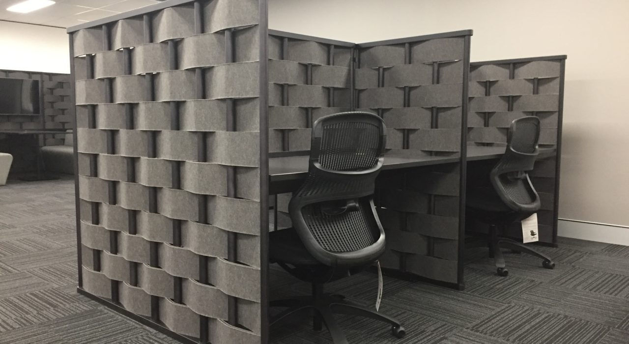 Studio shot of Bower privacy screening, showing two work stations side by side. Each desk has a new chair placed in front.