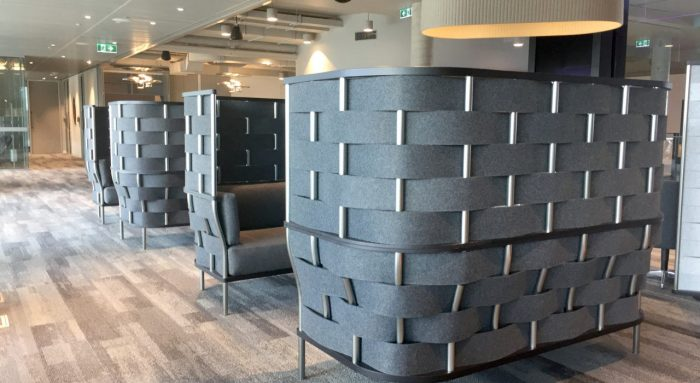 Studio shot of Bower screening wrapping two closed in seating areas of an office. Each screen wraps a comfortable couch, with each one facing one another within the area.
