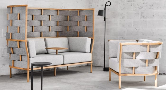 Studio shot of Bower screening in a casual seating area placed in the corner. Screening wraps a low backed chair as well as a two person couch. A small table platform comes out from the center of the couch.
