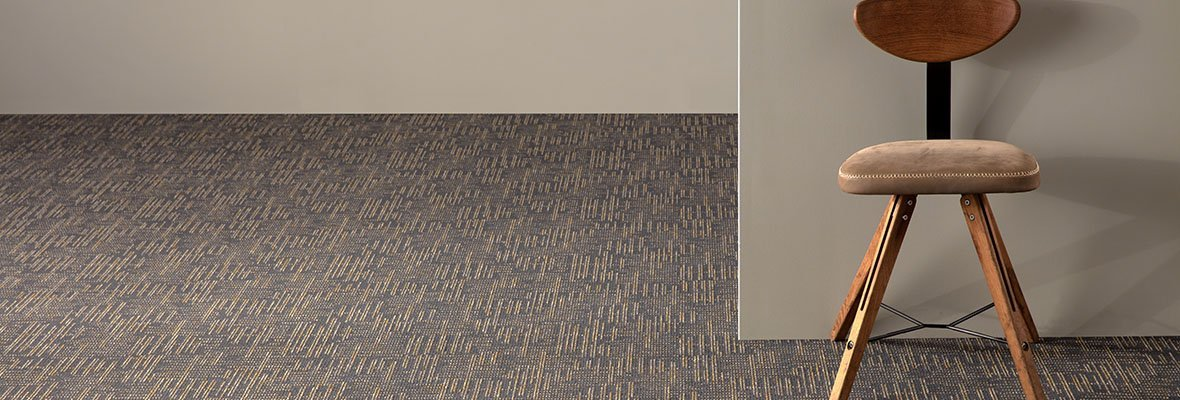 Studio shot looking into two rooms, using City Blocks II model carpeting. A wooden chair is placed against the wall.