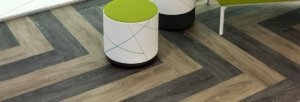 Studio shot of Classics luxury vinyl tile. A colorful Craquelure stool and bench comes into the shot from just ahead.