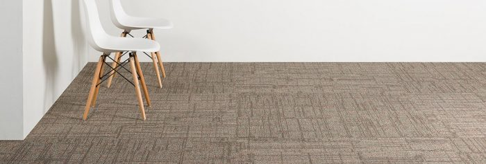 Studio shot of Impromptu model carpeting in a room. Against a gray wall, by the corner, are two wooden legged chairs.