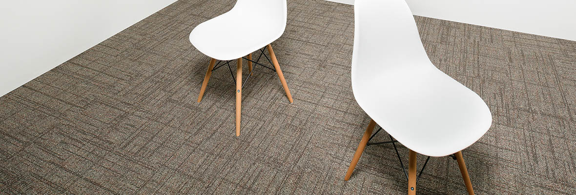 Studio shot of Impromptu carpeting with a grey wall. Two wooden legged chairs are faced in different directions.