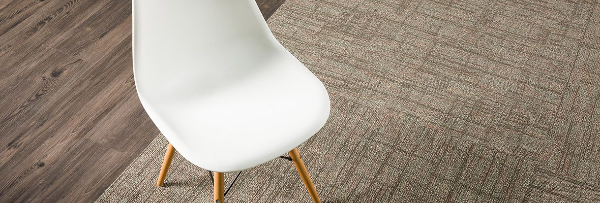 Studio shot of Impromptu carpeting, with a wooden floor adjacent. A wooden legged chair is placed at the edge of that carpet.