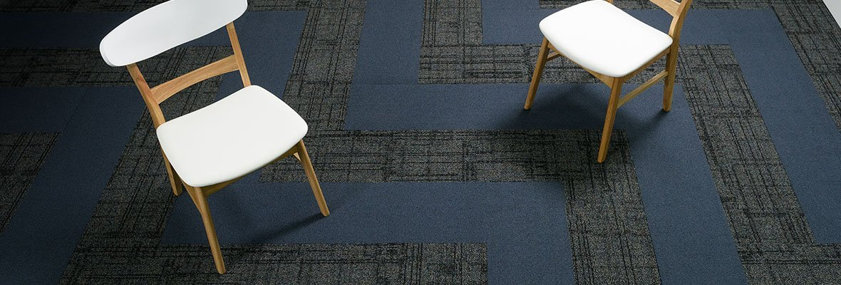 Studio shot of a room with two backed wooden leg chairs. Impromptu carpeting dresses the room with a solid color cutting through a herringbone pattern of the carpet.