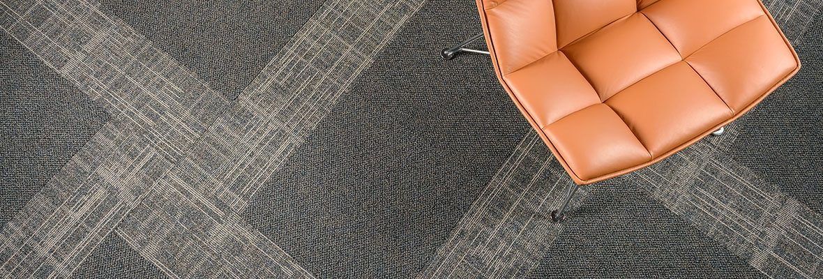 Studio shot of Impromptu carpeting, both sold and patterned. An orange PU cushioned chair is in the corner of this overhead composition.