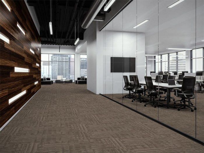 Outfitter carpet along a company corridor. There is glass walls to the left, looking into a large meeting space. At the end is guest seating looking out to the city.
