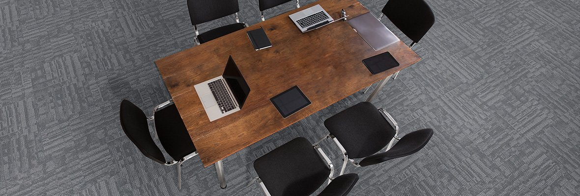 Studio shot from above a wooden table, with six chairs placed around. This area is dressed in Outfitter model carpeting.