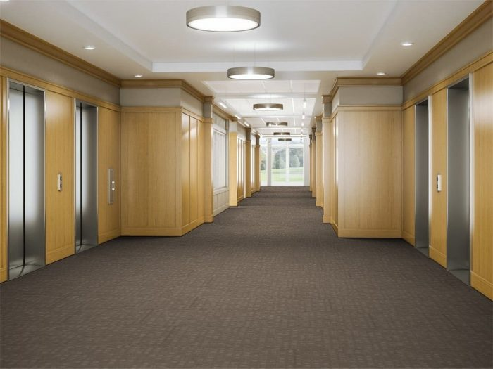 Looking down a hallway, leading to the elevator banks in a commercial building. The floor is lined in Oxford model carpeting.