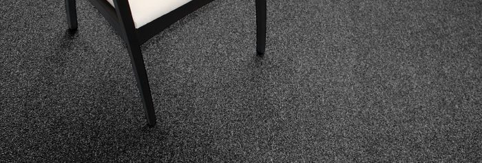 Studio shot of a black legged chair resting on Passages carpeting.