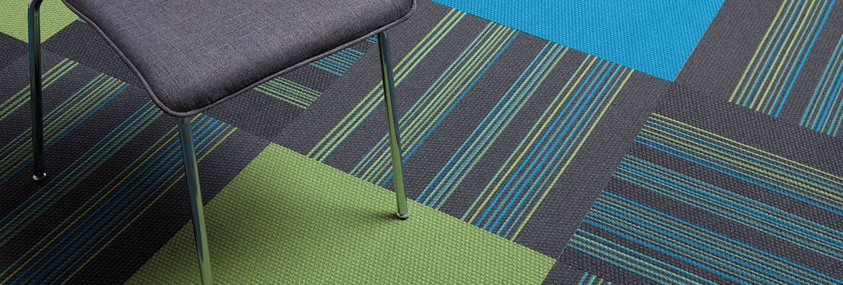 Studio shot of colorful Pop carpet squares, with a metal frame classroom chair set on top.