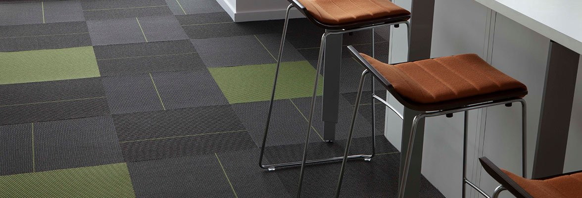 Studio shot of a classroom laboratory using Pop and Flash carpet squares. Each lab bench has 3 tall metal-framed bar stools pulled up to it.