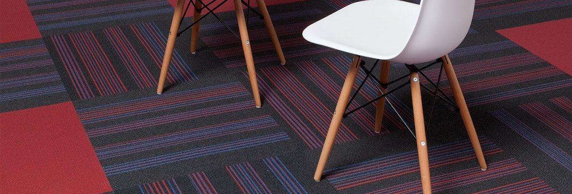 Closeup of Pop carpeting on the studio set. Two plastic chairs, with wooden legs are placed together. This room is also using many panels of Boom's Step Up color scheme.