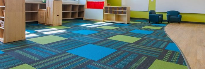 Studio photography inside a large classroom of the Lombard Early Childhood Center. Colorful squares of Pop carpeting are mixed in with the striped pattern of Boom carpet squares.