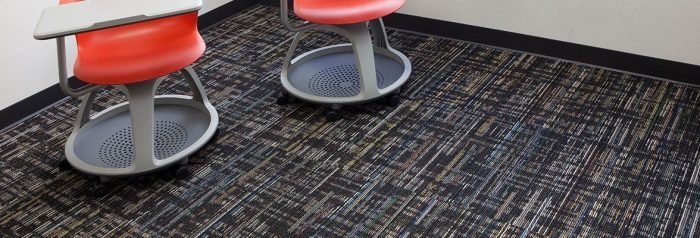 Studio shot of a two classroom desk chairs, resting atop Relativity carpeting. Each desk chair uses red plastic on the chair and grey desk top. They have a full platform for the feet, with wheels.