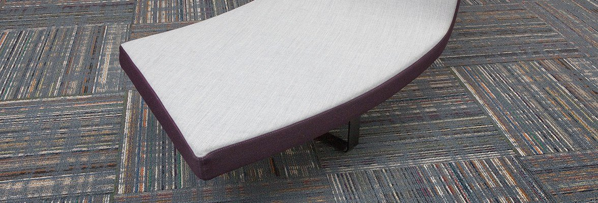 Studio shot of a curved bench, resting atop Relativity carpeting. Each square was given a quarter turn. The bench has been given a white cushion.