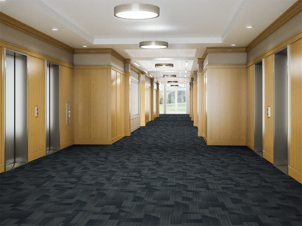 Looking down a hallway, leading to the elevator banks in a commercial building. The floor is lined in Skyline model carpeting.