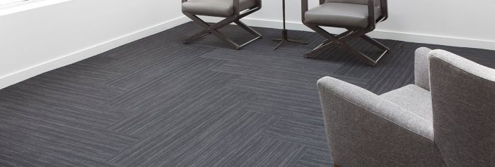 Studio photography of a waiting area, using Timber carpeting. It is arranged in a herringbone pattern.