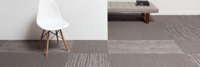 Studio photography, looking into a room lined with solid colored carpeting, with Timber planks breaking up the design. A white plastic chair has been placed against the wall, with a long cushioned bench against the wall behind.