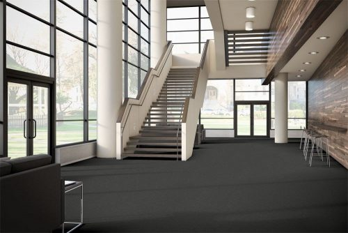 Tone model flooring on the floor of a company lobby. A long set of stairs leads upward. Tall backed chairs are placed along the wall, opposite the door.