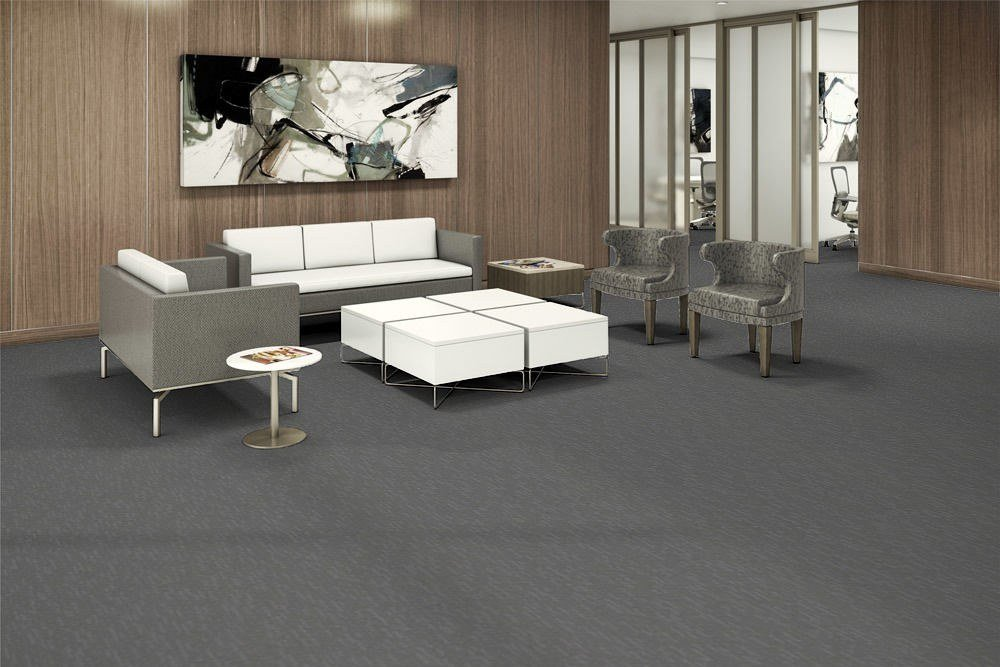 Tone model flooring in a large lounge area. A wide abstract painting hangs over a long couch. A paneled coffee table is placed in front, with mid-backed chairs on each side.