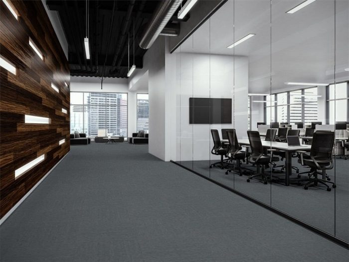 Transit carpet along a company corridor. There is glass walls to the left, looking into a large meeting space. At the end is guest seating looking out to the city.