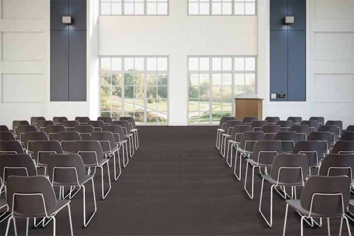 Flooring in a large lecture hall, using Transit's Gate color choice. A center aisle divides rows of medium backed metal framed chairs. Two windows in front look out to a grassy field.