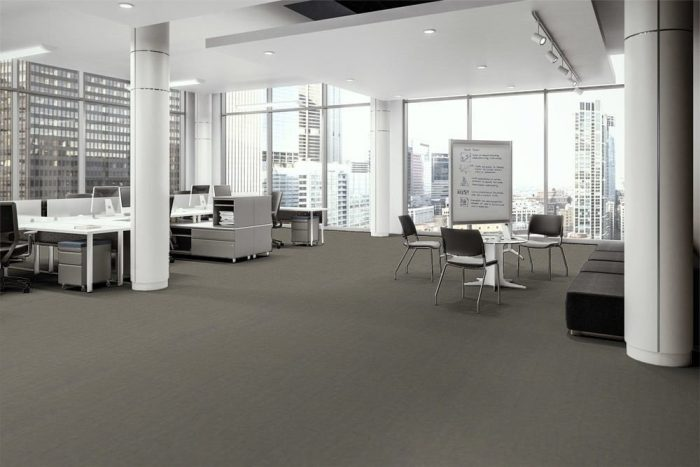 Transit flooring in the open office. At one side are occupied work desks with attached credenzas. A portable white board is placed to the side of one round cafe table, with instructions written upon it. The full height windows look out to the city.