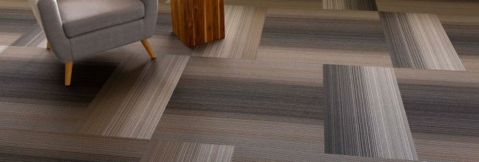 Studio shot of Umbra II carpeting in a grey herringbone pattern. On the left is a wooden cubic end table, with a cushioned chair beside.