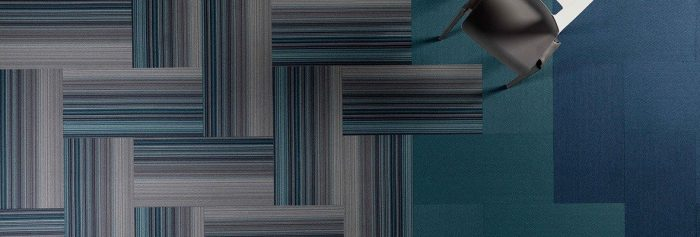 Studio shot of Umbra II carpeting from overhead. The herringbone pattern meets with other solid color carpeting.