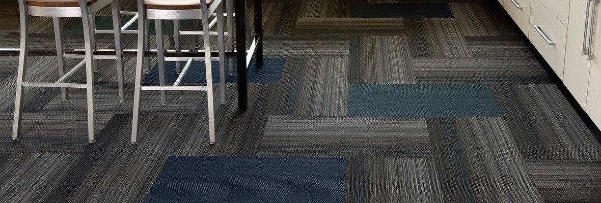 Studio shot of Umbra II carpeting in a classroom laboratory. The herringbone pattern is broken up with solid carpet squares. At the side, you can see one of the classroom benches, with tall chairs placed.