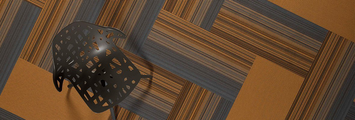 Studio shot of a dark grey plastic chair, resting on Umbra II carpeting. The carpet squares are arranged in a herringbone design. The chair's seat and back has been given a stylish cutout aesthetic.